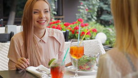 Cute girlfriend talking. Women on the terrace of a cozy cafe rejoices meeting stock video