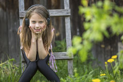 Cute girlie enjoys music with headphones Royalty Free Stock Photography