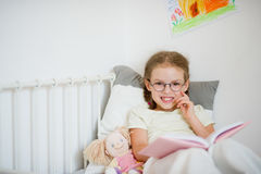 Cute girlie in glasses reading a book while lying in bed. Next to her sits a doll. Bright children's drawing on a white wall. The girl looks into the camera stock photos