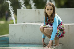 Cute girlie plays near the city fountain. Walking. Royalty Free Stock Image
