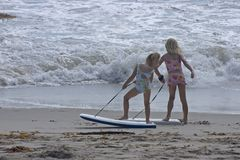 Cute girls at the beach. Two young girls play with their boogie boards at the beach stock images