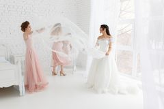 Cute girls celebrating a bride`s bachelorette party and playing with veil in bedroom stock photography