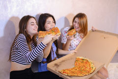 Cute girls cool spend time and enjoy pizza, sit on floor in brig stock photos