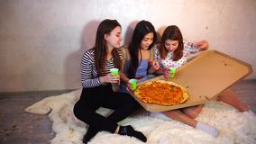 Cute girls cool spend time and enjoy pizza, sit on floor in bright bedroom in evening. stock video footage