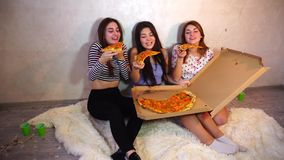 Cute girls cool spend time and enjoy pizza, sit on floor in bright bedroom in evening. stock footage