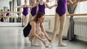 Cute girls diligent students of ballet school are stretching legs practising basic positions while their instructor is stock footage
