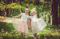 Cute girls in the forest. Two beautiful little girls posing in spring forest full of white blossoming garlic flowers Royalty Free Stock Photography