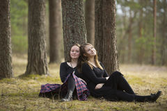 Cute girls friends sitting in the forest. Walking. Royalty Free Stock Photos