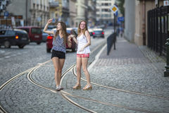 Cute girls are fun fooling around in the middle of the streets of the old town. Royalty Free Stock Images