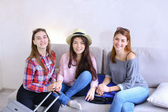Cute girls going on trip and preparing suitcases on couch in aft. Funny female friends together collect large gray and blue suitcases, add up all necessary Stock Image
