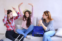 Cute girls going on trip and preparing suitcases on couch in aft. Funny female friends together collect large gray and blue suitcases, add up all necessary Stock Photo