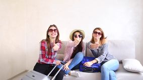 Cute girls going on trip and preparing suitcases on couch in afternoon room. Funny female friends together collect large gray and blue suitcases, add up all stock video
