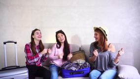 Cute girls going on trip  preparing suitcases on couch in afternoon room. Funny female friends together collect large gray and blue suitcases, add up all stock video footage