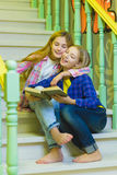 Cute girls with holding book and sitting on stairs of ladder indoor Stock Image