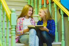 Cute girls with holding book and sitting on stairs of ladder indoor Royalty Free Stock Photos