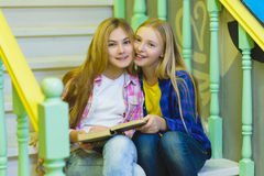 Cute girls with holding book and sitting on stairs of ladder indoor Stock Photo