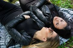 Cute girls lying down on the blanket and talking in a green meadow on a spring day in nature. A girl wears sunglasses and a black jacket. Relaxation and enjoy stock image