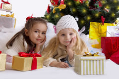 Cute girls lying under Christmas tree with gifts Stock Photos