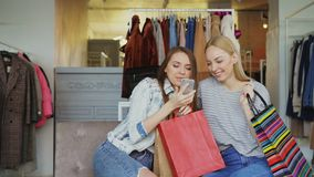 Cute girls are making selfie with colourful paper bags in women`s clothing boutique using smartphone, then watching. Cute girls are sitting and making selfie stock video