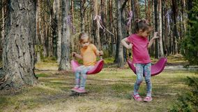 Cute girls play with colorful swings in the forest. Two cute girls play with colorful swings in the forest in summer stock video footage