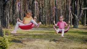 Cute girls play with colorful swings in the forest. Two cute girls play with colorful swings in the forest in summer stock footage