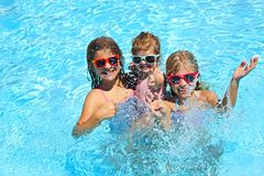 Cute girls playing in swimming pool. Summer vacation and travel concept stock image
