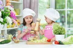 Cute girls preparing delicious fresh salad in kitchen. At home
