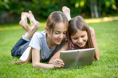 Cute girls relaxing on grass at park and using digital tablet Royalty Free Stock Photography