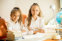 Cute girls in school uniform sitting at desk and doing homework Royalty Free Stock Image