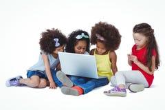 Cute girls sitting on the floor using laptop Stock Photos