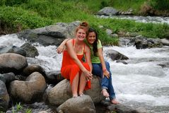 Cute girls sitting by rapids Stock Photos