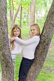 Cute girls in summer sit on tree Royalty Free Stock Image