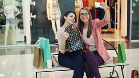 Cute girls are taking selfie in shopping mall posing with paper bags and trendy hand gestures sitting on bench in stock footage