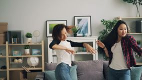 Cute girls in trendy jeans are dancing at home together listening to music and having fun. Multiracial friendship stock footage