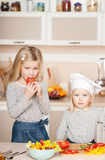 Cute girls trying to cook salad and help mother Royalty Free Stock Photos
