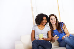 Cute girls watching TV. Portrait of two cute girls watching TV on a sofa Royalty Free Stock Photos