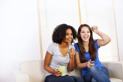 Cute girls watching TV. Portrait of two cute girls watching TV on a sofa Royalty Free Stock Photography