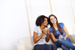 Cute girls watching TV. Portrait of two cute girls watching TV on a sofa Royalty Free Stock Image