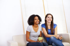 Cute girls watching TV. Portrait of two cute girls watching TV on a sofa Royalty Free Stock Photo