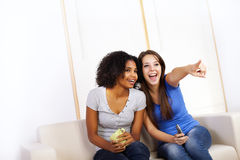 Cute girls watching TV. Portrait of two cute girls watching TV on a sofa Stock Image