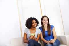Cute girls watching TV. Portrait of two cute girls watching TV on a sofa Stock Photos