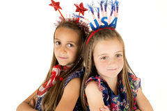 Cute girls wearing American patriotic headbands back to back Royalty Free Stock Photos