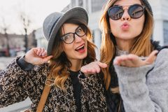 Cute girls wearing elegant glasses sending air kiss while spending time in weekend together. Charming friends having fun royalty free stock photos