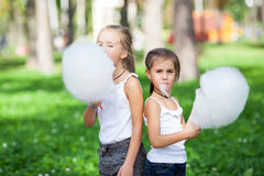Cute girls with white cotton candy Stock Images