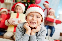 Cute gnome. Image of cute lad in Santa cap looking at camera with company of friends behind Stock Photography