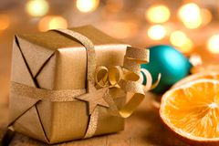 Cute golden Christmas present with lights. Cute golden Christmas present with orange slices and lights on old wood - bokeh effect Royalty Free Stock Images