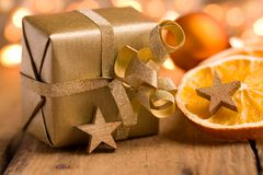 Cute golden Christmas present on wood. Cute golden Christmas present with stars and orange slices on wood - bokeh effect Royalty Free Stock Image
