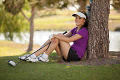 Cute golfer resting under a tree Stock Image