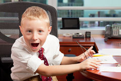 Cute goofy boy in office. Cute blond boy with a goofy expression wearing business attire in a corporate office setting Stock Photos