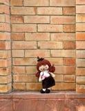 Cute graduation girl doll standing on brick background. Cute graduation lady girl doll standing on brick background Stock Image